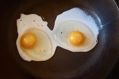 Chiuda su due uova fritte sul fondo nero della pentola fotografie stock