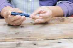 Chiuda su facendo uso del lancelet sul dito a controllare il livello della glicemia dal metro del glucosio immagini stock libere da diritti