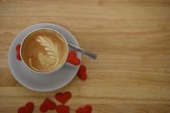 Chiuda su fotografia della bevanda di una tazza di caffè calda fresca con le decorazioni rosse del cuore di amore sulla tavola pe Fotografia Stock