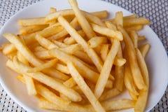 Chiuda su Fried French Fries in piatto bianco Fotografia Stock Libera da Diritti