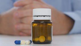Chiuda su fucilazione con il dottore Hands e pillole colorate sulla Tabella archivi video