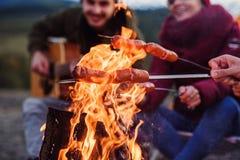 Chiuda su fuoco di accampamento e sulla società degli amici che salsiccie bollenti là Stanno bevendo le bevande di energia, canto fotografia stock