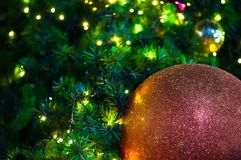 Chiuda su grande natale rosso della palla di scintillio sull'albero con il fondo della luce bianca del cavo immagine stock