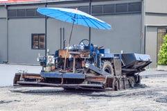 Chiuda su indietro del macchinario blu per portare la piccola pietra con misto con l'asfalto per il versamento sul pavimento per  fotografia stock