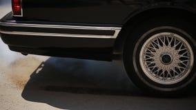 Chiuda su indietro dell'automobile nera che inizia a guidare, lasciando in via stock footage