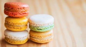 Chiuda su macaron francese o italiano variopinto sulla tavola di legno con la c Fotografia Stock
