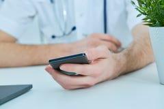 Chiuda su medico maschio o sullo studente di medicina che utilizza lo Smart Phone mobile che lavora al computer portatile nell'os Fotografie Stock Libere da Diritti