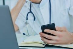 Chiuda su medico maschio o sullo studente di medicina che utilizza lo Smart Phone mobile che lavora al computer portatile nell'os Fotografie Stock