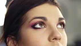 Chiuda su metraggio di creare lo sguardo affumicato perfetto degli occhi Bei occhi della nocciola di una ragazza castana attraent video d archivio