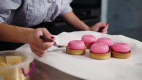 Chiuda su metraggio di un confettiere che decora i dessert rosa della glassa I dessert sono sulla tavola di funzionamento, copert video d archivio