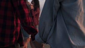 Chiuda su metraggio di una coppia che si tiene per mano insieme mentre camminano sulla spiaggia Lle altre coppie su una prospetti stock footage