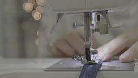 Chiuda su metraggio di una donna che cuce un grembiule con una macchina per cucire archivi video