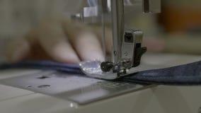 Chiuda su metraggio di una donna che cuce un grembiule con una macchina per cucire video d archivio