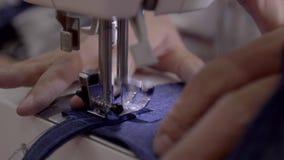 Chiuda su metraggio di una donna che cuce un grembiule con una macchina per cucire stock footage