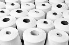 Chiuda su molte bobine del filato dentro in una fabbrica del tessuto, il tessuto i fotografie stock