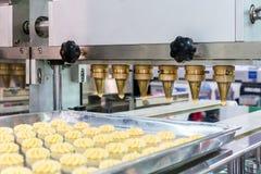 Chiuda su pasta o su crema e doti lo scarico d'un polverizzatore del biscotto o dei dolci automatici che fa la macchina nella lin fotografia stock
