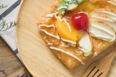 Chiuda su, pasticcerie danesi di vista superiore con frutta sul piatto di legno Immagini Stock Libere da Diritti