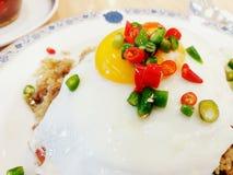Chiuda su peperoncino caldo rosso e verde affettato sull'uovo fritto superiore con il riso del basilico della carne tritata sul p Fotografia Stock