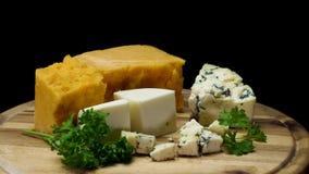 Chiuda su per i formaggi invecchiati deliziosi francesi choped e servito sul bordo di legno isolato su fondo nero Pagina stock footage