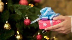 Chiuda su per la mano femminile che tiene il regalo di Natale in carta da imballaggio rossa con il grande, nastro blu Mano della  archivi video
