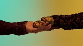 Chiuda su per la mano orientale dell'uomo che dà una grande pepita di oro ad un altro uomo, isolato su fondo verde e giallo azion fotografie stock libere da diritti
