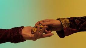 Chiuda su per la mano orientale dell'uomo che dà una grande pepita di oro ad un altro uomo, isolato su fondo verde e giallo azion fotografia stock libera da diritti