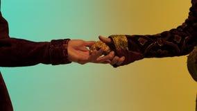 Chiuda su per la mano orientale dell'uomo che dà una grande pepita di oro ad un altro uomo, isolato su fondo verde e giallo azion immagini stock