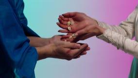 Chiuda su per le mani orientali della giovane donna che danno molte piccole conchiglie alle mani dell'uomo, concetto di baratto a archivi video