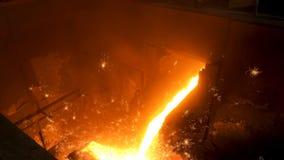 Chiuda su per metallo fuso versato dalla siviera per fondere alla fonderia Metraggio di riserva Fusione della colata del metallo immagine stock