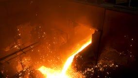 Chiuda su per metallo fuso versato dalla siviera per fondere alla fonderia Metraggio di riserva Fusione della colata del metallo fotografie stock libere da diritti