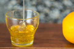 Chiuda su piccolo vetro che si siede sullo scrittorio di legno con miele che cade in da sopra, limone dal lato Fotografia Stock Libera da Diritti