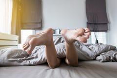Chiuda su a piedi nudi sotto della coperta, dei piedi e dell'allungamento pigro sul letto Immagini Stock Libere da Diritti