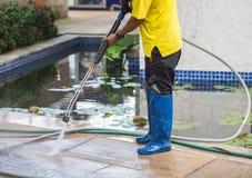 Chiuda su pulizia all'aperto del pavimento con il getto di acqua ad alta pressione Fotografie Stock Libere da Diritti