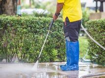 Chiuda su pulizia all'aperto del pavimento con il getto di acqua ad alta pressione Immagine Stock