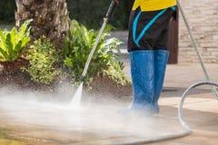 Chiuda su pulizia all'aperto del pavimento con il getto di acqua ad alta pressione Fotografia Stock
