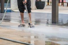 Chiuda su pulizia all'aperto del pavimento con il getto di acqua ad alta pressione Fotografie Stock