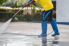 Chiuda su pulizia all'aperto del pavimento con il getto di acqua ad alta pressione Fotografia Stock Libera da Diritti