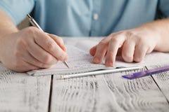 Chiuda su scrittura maschio sulla carta, il per la matematica sudicio di scrittura, stude della mano del ` s Fotografia Stock