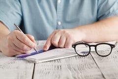 Chiuda su scrittura maschio sulla carta, per la matematica sudicio della mano del ` s di scrittura, studen Immagine Stock