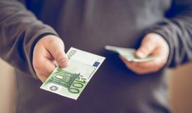 Chiuda su soldi dentro equipaggia la mano Uomo che dà cento euro Profondità del campo poco profonda Fotografie Stock