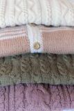 Chiuda su su 4 maglioni o saltatori eleganti della lana nella colonna Immagine Stock
