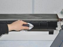 Chiuda su su pulizia del condizionatore d'aria con la spazzola Immagine Stock