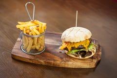 Chiuda su su un hamburger e sulle patate fritte del formaggio Immagine Stock