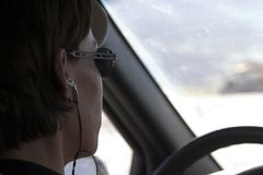 Chiuda in su su una donna che guida con una cuffia avricolare sopra fotografia stock libera da diritti