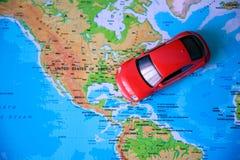Chiuda su su una mano che dispone un perno su un segno del giocattolo dell'automobile e della mappa dove andare Immagine Stock Libera da Diritti