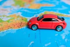 Chiuda su su una mano che dispone un perno su un segno del giocattolo dell'automobile e della mappa dove andare Immagine Stock