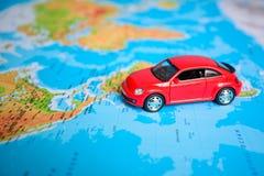 Chiuda su su una mano che dispone un perno su un segno del giocattolo dell'automobile e della mappa dove andare Fotografia Stock