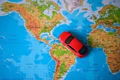 Chiuda su su una mano che dispone un perno su un segno del giocattolo dell'automobile e della mappa dove andare Immagini Stock