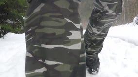 Chiuda su sugli stivali che camminano nella neve profonda dell'inverno in foresta stock footage