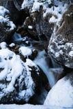 Chiuda su sul fiume del ruscello della montagna che scorre fra le rocce coperte di neve immagine stock